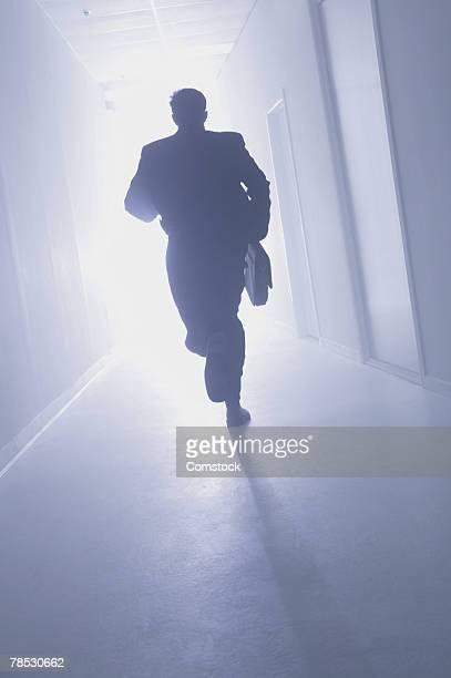 Businessman running down hallway toward light