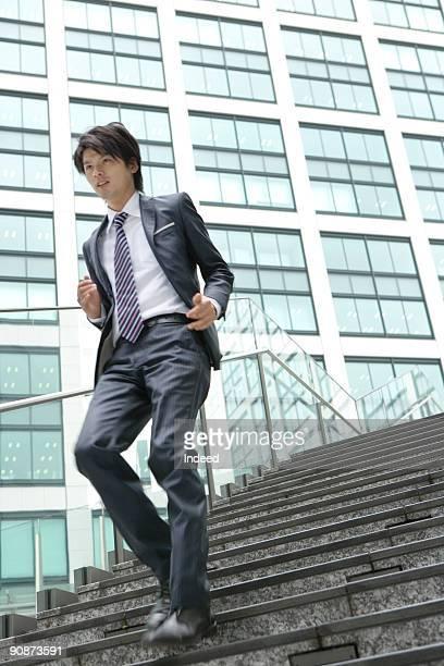Businessman running down stair