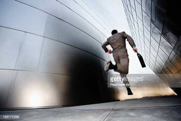 Businessman running down urban alley