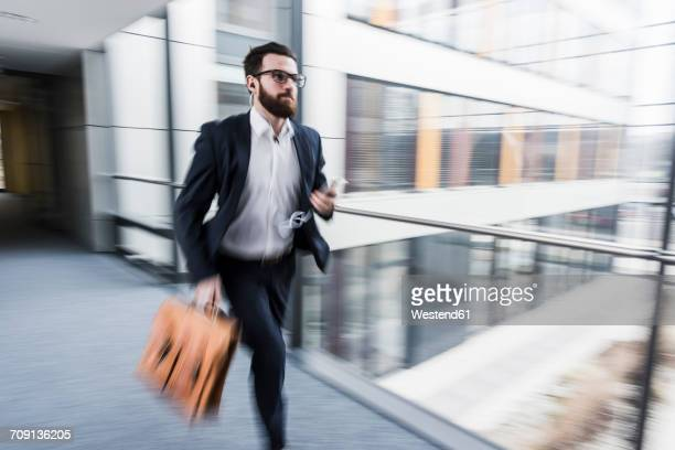 businessman running in corridor of an office building - dringendheid stockfoto's en -beelden