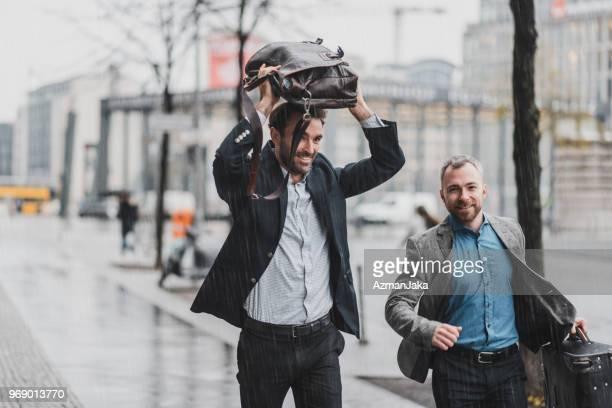 geschäftsmann laufen im regen halten einen koffer und eine aktentasche - regen stock-fotos und bilder