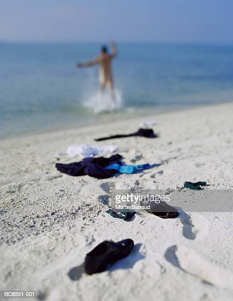 Businessman running into sea, rear view (focus on clothes in fore)