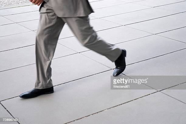 Businessman running, low section, (blurred motion)
