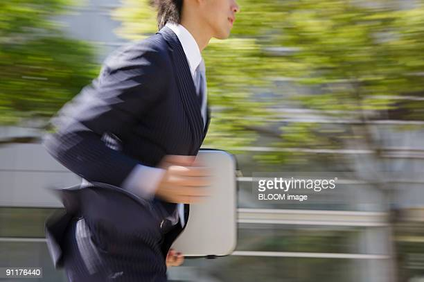 Businessman running, mid section, side view