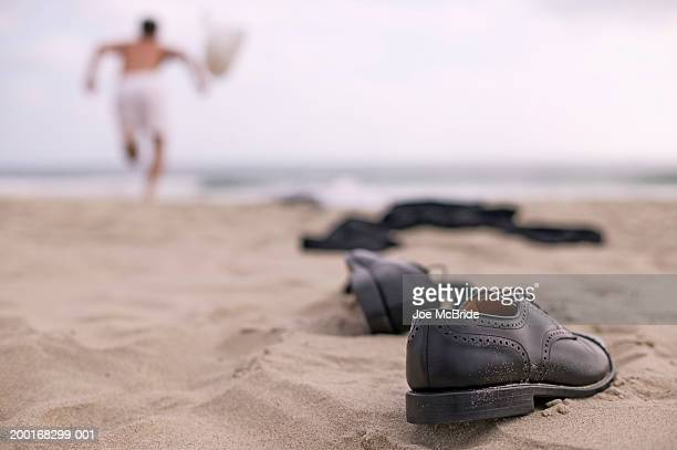 Businessman running on beach, shoes and clothes on sand