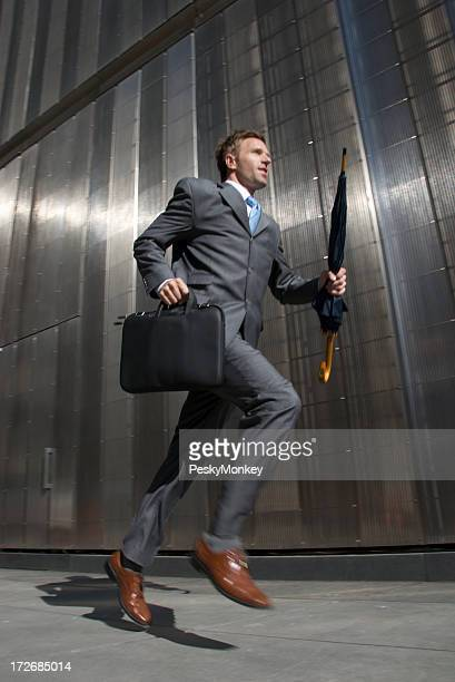 Geschäftsmann läuft auf Stadt Gehweg vor den glänzenden Wall