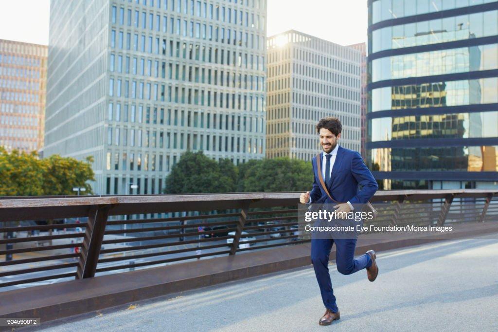 Businessman running on city street : Stock Photo