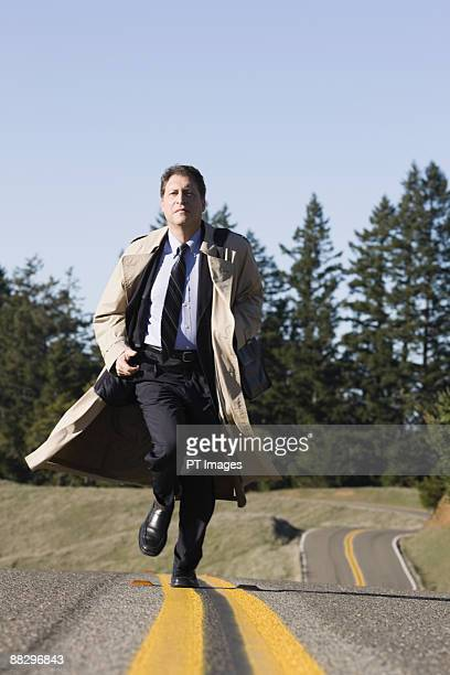 businessman running on remote road - trench coat stock pictures, royalty-free photos & images