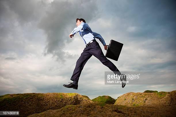 Businessman running over rocks