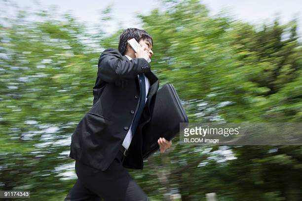 Businessman running, talking on mobile phone