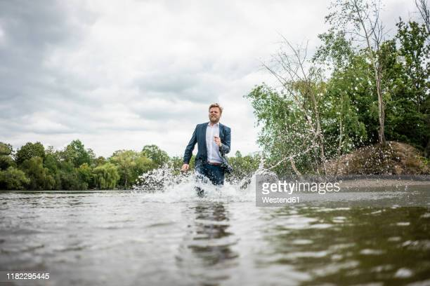 businessman running through a lake - runaway stock pictures, royalty-free photos & images