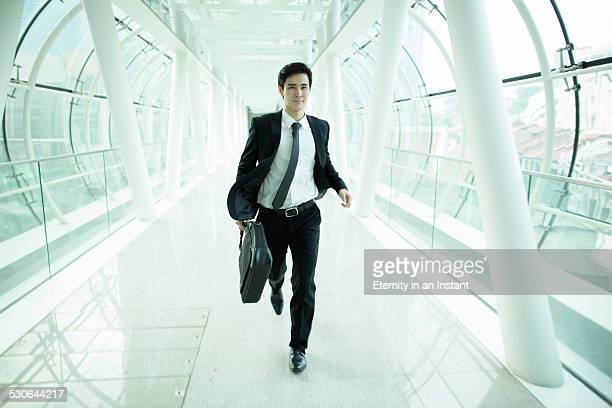 Businessman running through glass tunnel