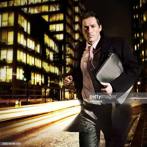 businessman running through street, night (digital composite) - solo un uomo foto e immagini stock