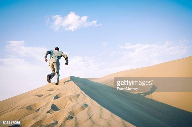 Businessman Running Up Desert Sand Dune