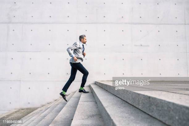 businessman running up stairs outdoors - steps stock pictures, royalty-free photos & images