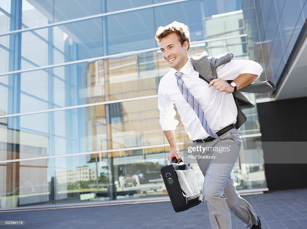 Businessman running with briefcase : Stock Photo
