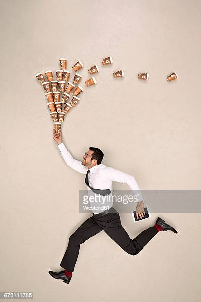 Businessman running with coffee and tablet
