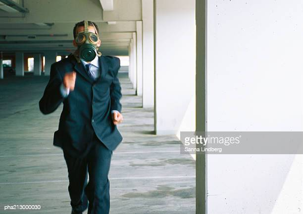 Businessman running with gas mask covering face