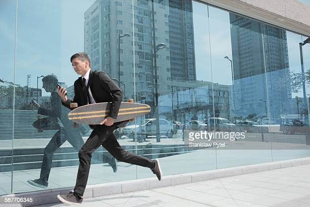 Businessman running with longboard in city