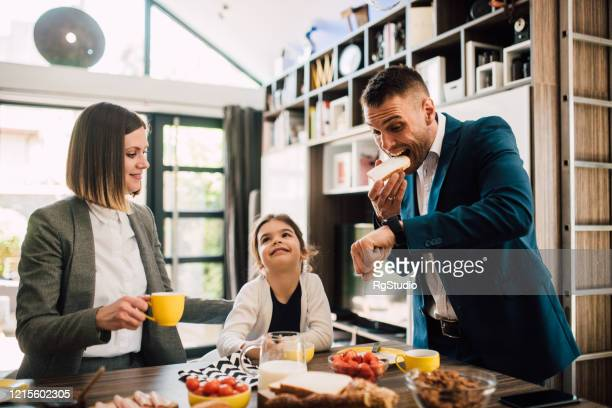 businessman rushing for work during family breakfast - urgency stock pictures, royalty-free photos & images