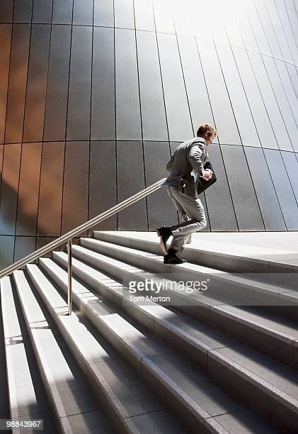 businessman rushing up steps outdoors - stairs stock photos and pictures
