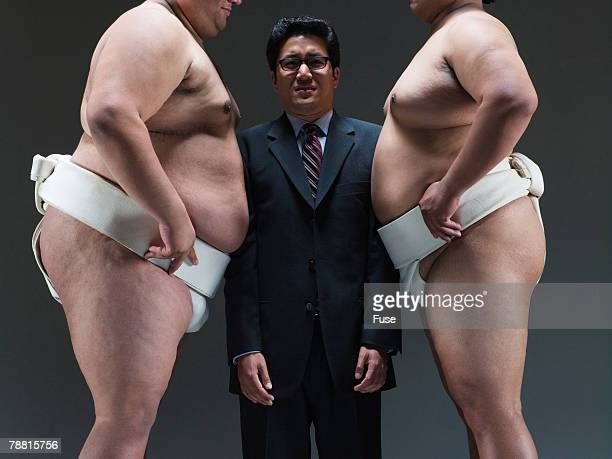Businessman Sandwiched Between Sumo Wrestlers
