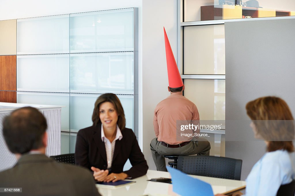 Businessman sat in corner with dunce cap : Stock Photo