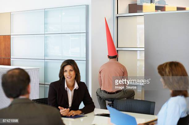businessman sat in corner with dunce cap - idiots stock pictures, royalty-free photos & images