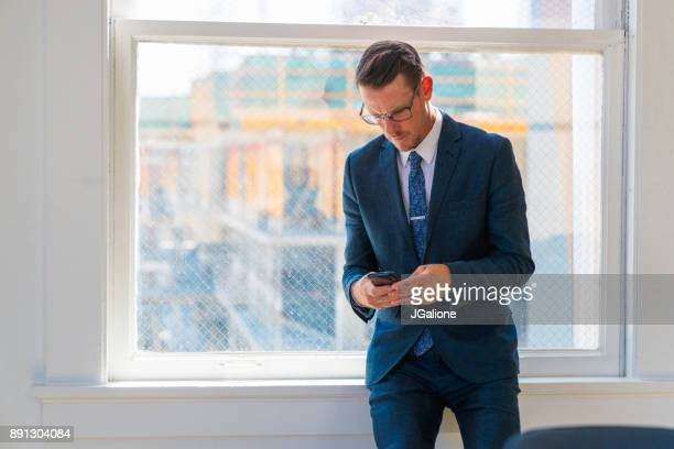 Businessman sat on a window ledge using his mobile phone