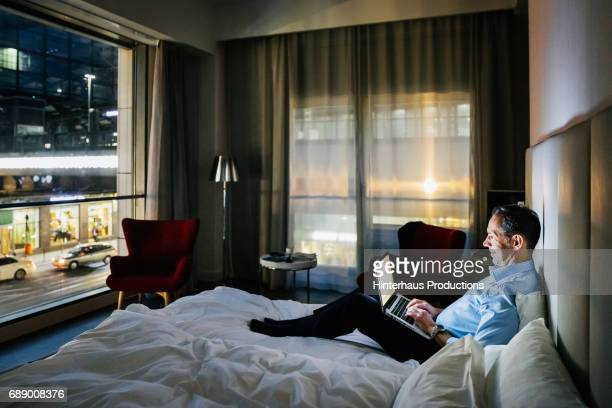 Businessman Sat On Hotel Bed Working