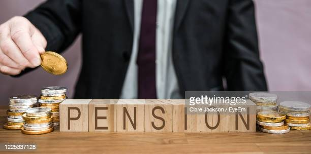 a businessman saving for pension by contributing money from his salary, savings, wages, income fund - saving stock pictures, royalty-free photos & images