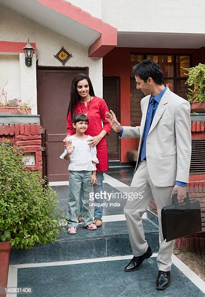 Businessman saying goodbye to his wife and daughter