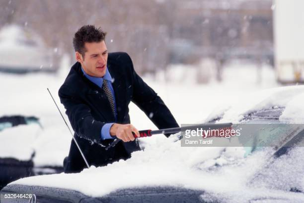 Businessman Scraping Snow off Car