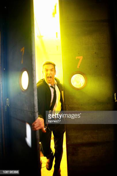 businessman screaming and running through a pair of doors - industrial door stock pictures, royalty-free photos & images