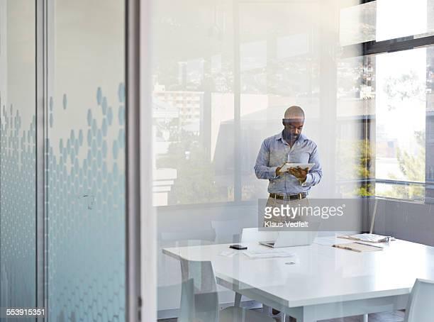 Businessman scrolling on tablet in meetingroom