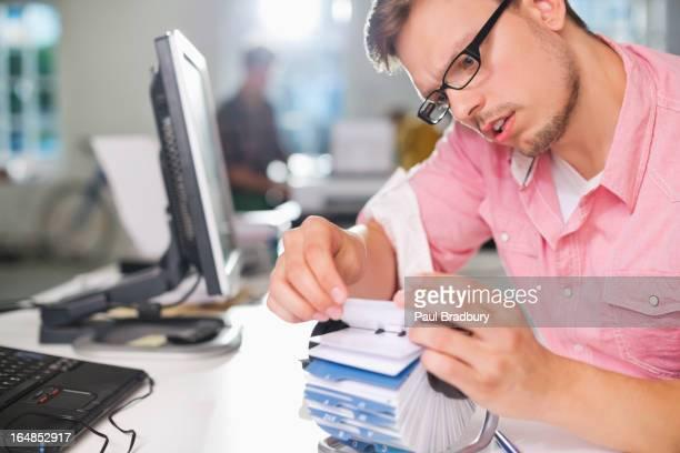 Businessman searching for address on desk