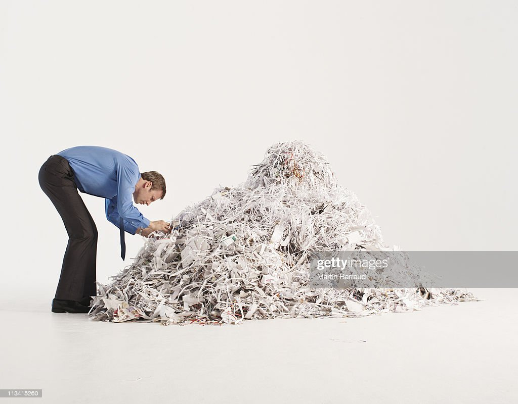Businessman searching in pile of shredded paper : Stock Photo