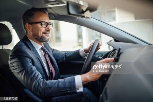 businessman searching location phone while driving a car - driver stock pictures, royalty-free photos & images