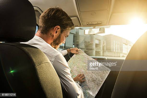 Businessman searching the direction on a map in the car.