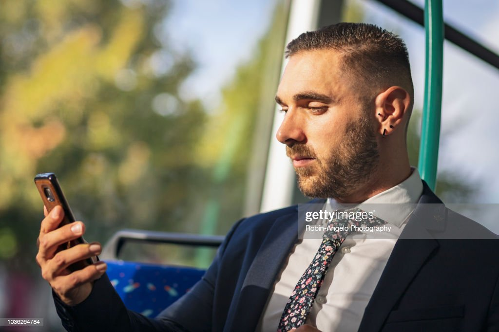 businessman seat in a tramway and looking his phone : Stock Photo