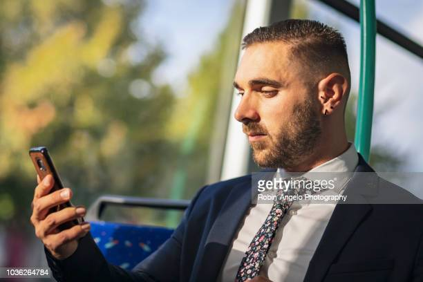 businessman seat in a tramway and looking his phone