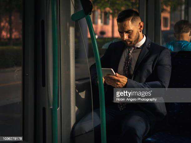 businessman seat in a tramway and looking his tablet