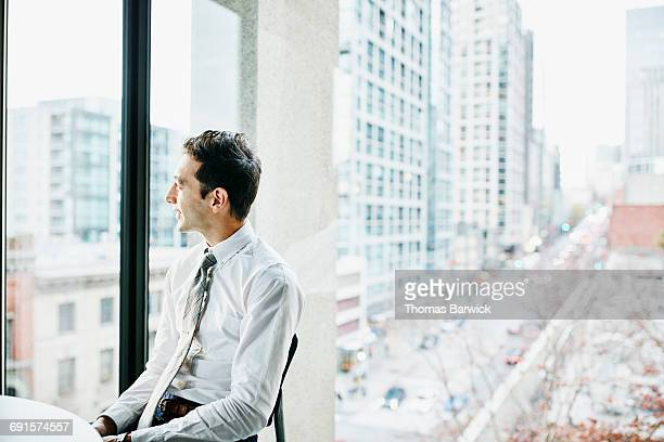 Businessman seated in office looking out window