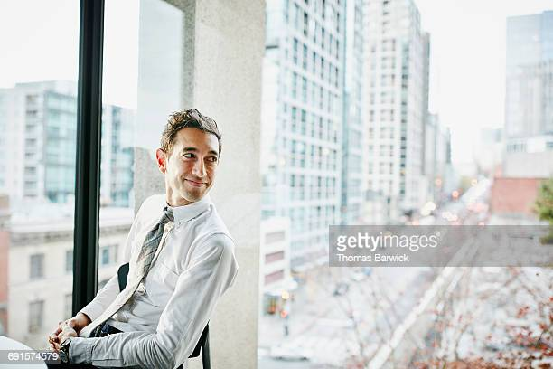 Businessman seated in office with view of city