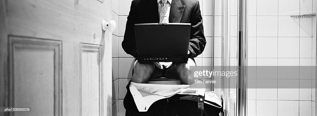 Businessman seated on the toilet, with a laptop computer, B&W : Stock Photo