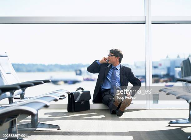 Businessman seating on airport floor talking on cell phone