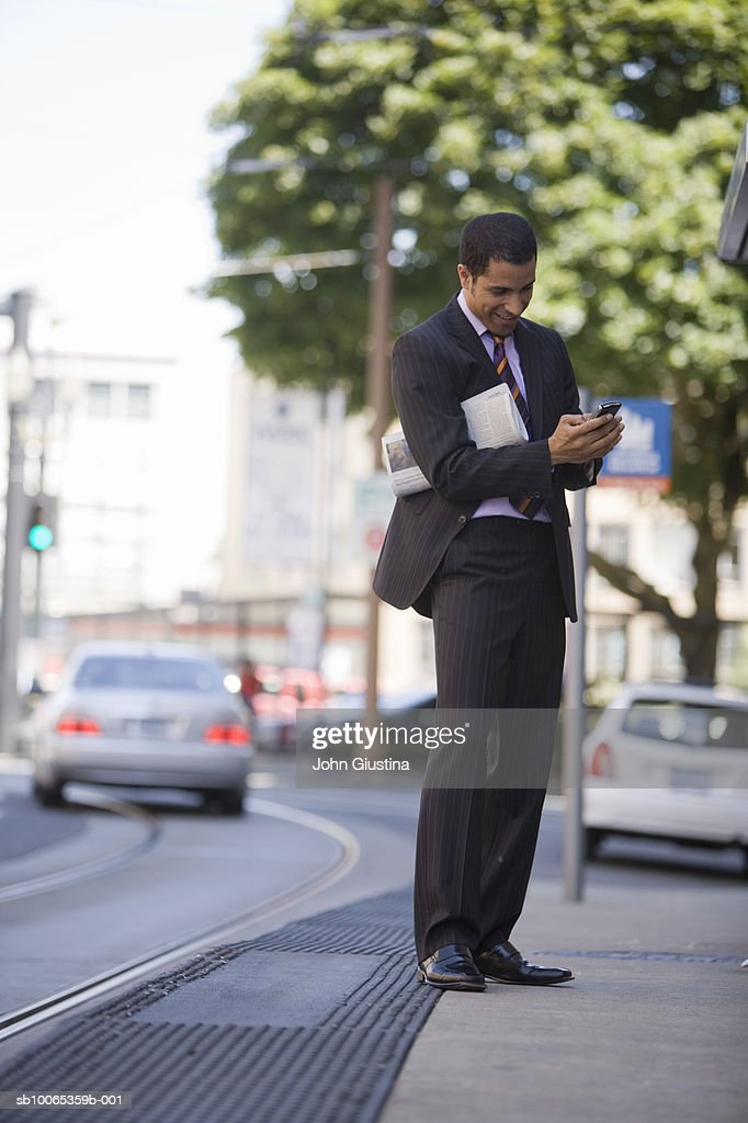 Businessman sending text messages on city street : Foto stock