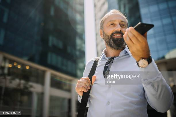 businessman sending voice message while leaving business building - speech recognition stock pictures, royalty-free photos & images