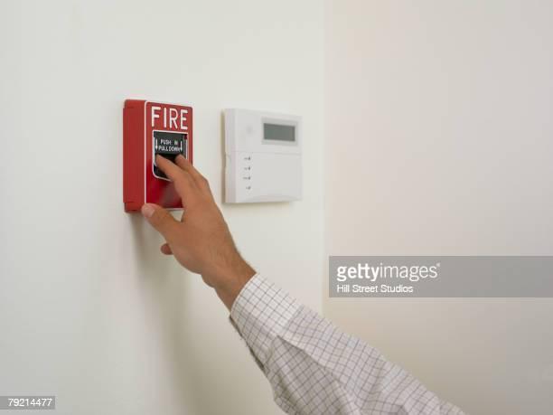 Businessman setting off the fire alarm