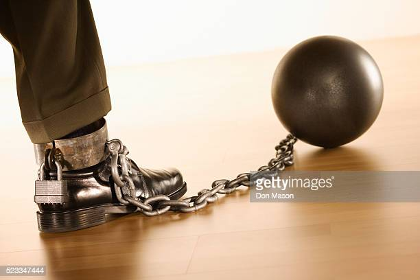 Businessman Shackled to Ball and Chain